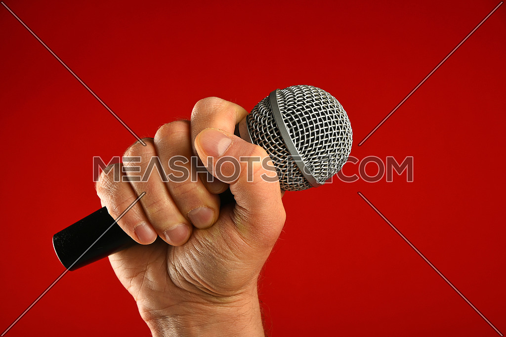 Man hand holding voice microphone in fist over red background, side view