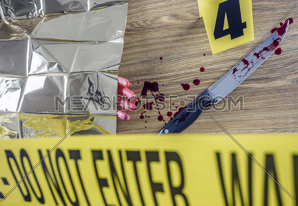 Murder scene for cutting weapon, gory hand along with a knife with blood, conceptual image
