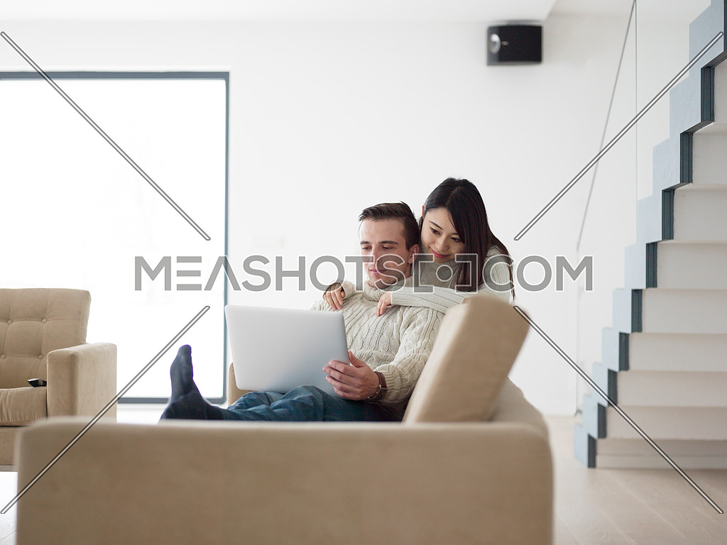 Young multiethnic couple relaxing at luxury home using laptop computer reading in the living room on the sofa couch.