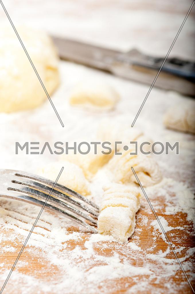 making fresh Italian potato gnocchi on a wood rustic table