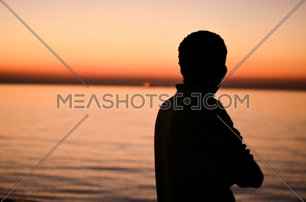 A guy standing at the beach enjoying his time and relaxing during sunset time