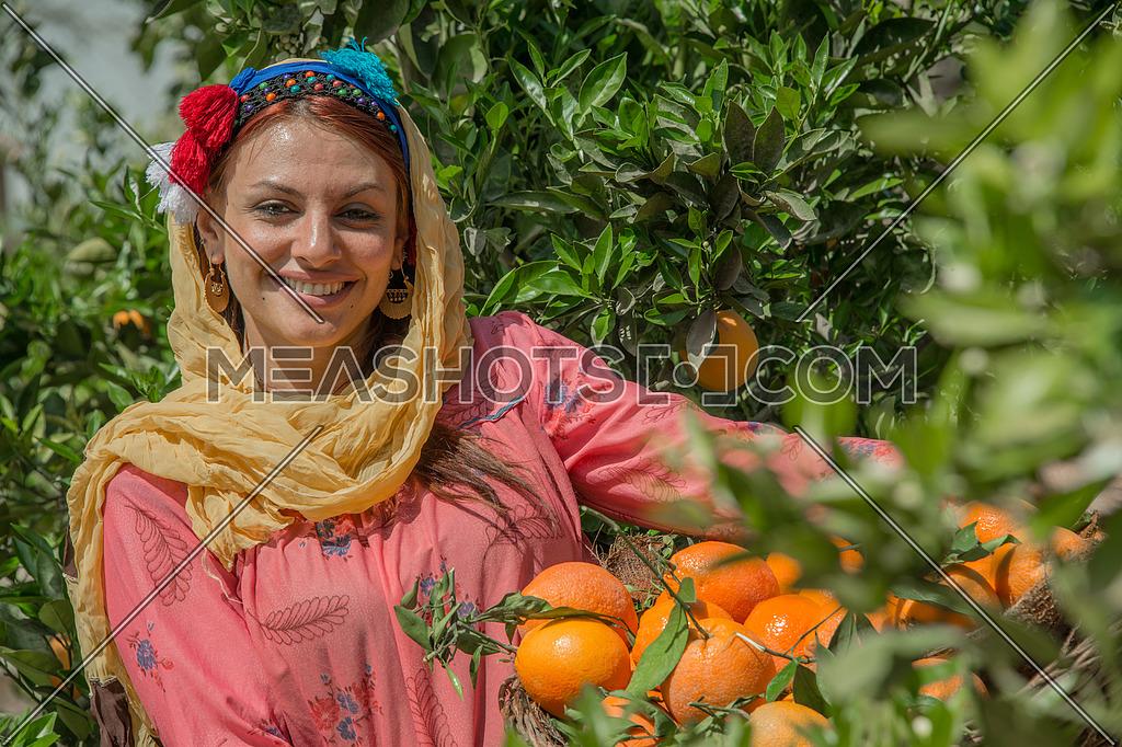 An egyptian female farmer carrying a basket full of tangerine