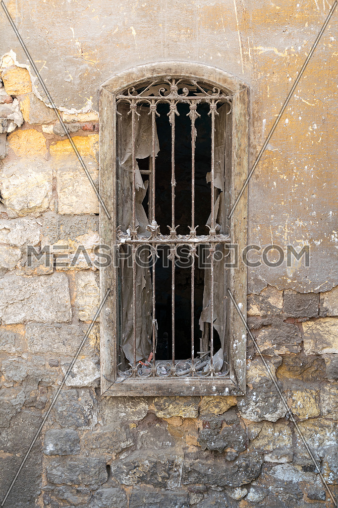 Old abandoned wall with one closed wooden window covered by broken wooden iron grid, Old Cairo, Egypt