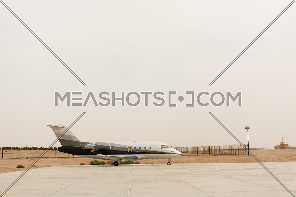 Modern private jet in Middle East airport in the desert