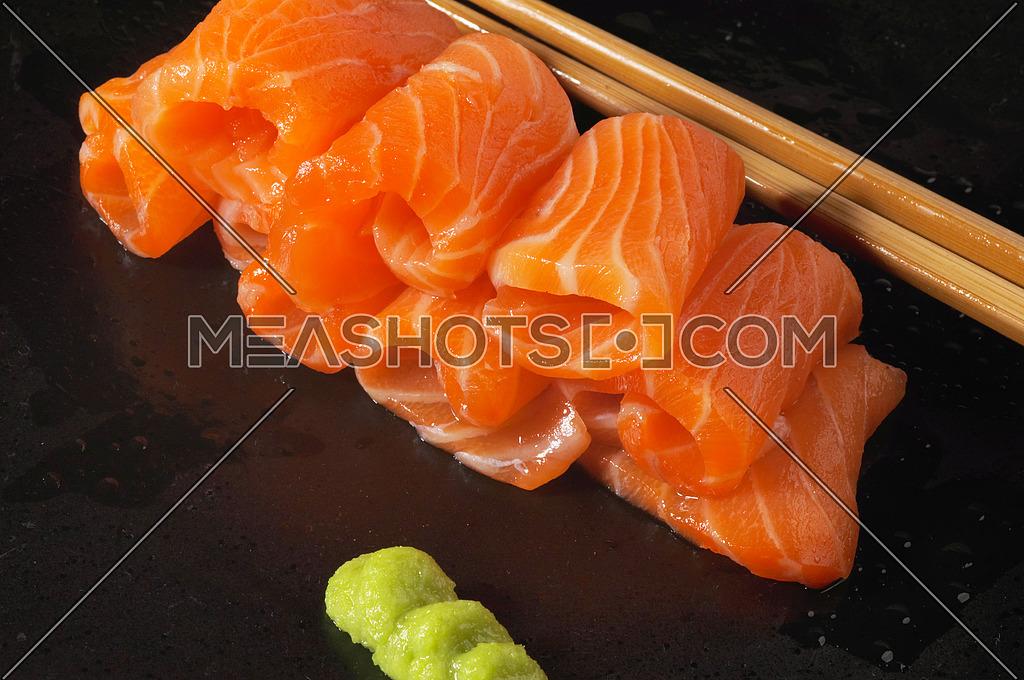 slice of salmon sushi with wasabi sauce