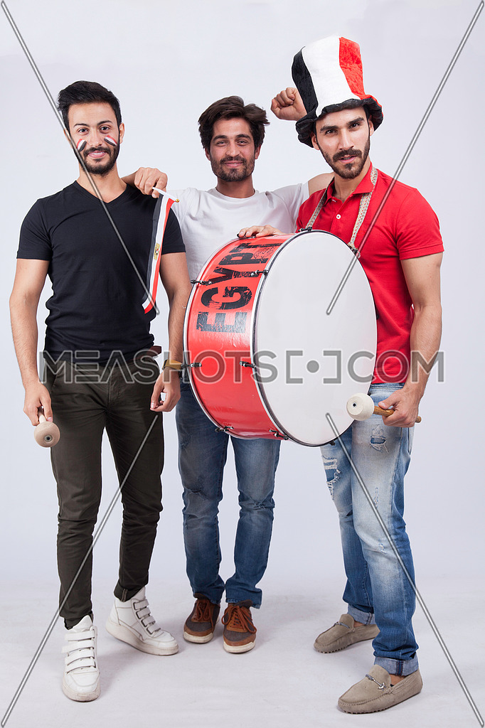 Three young men standing on a white background cheering with a drum