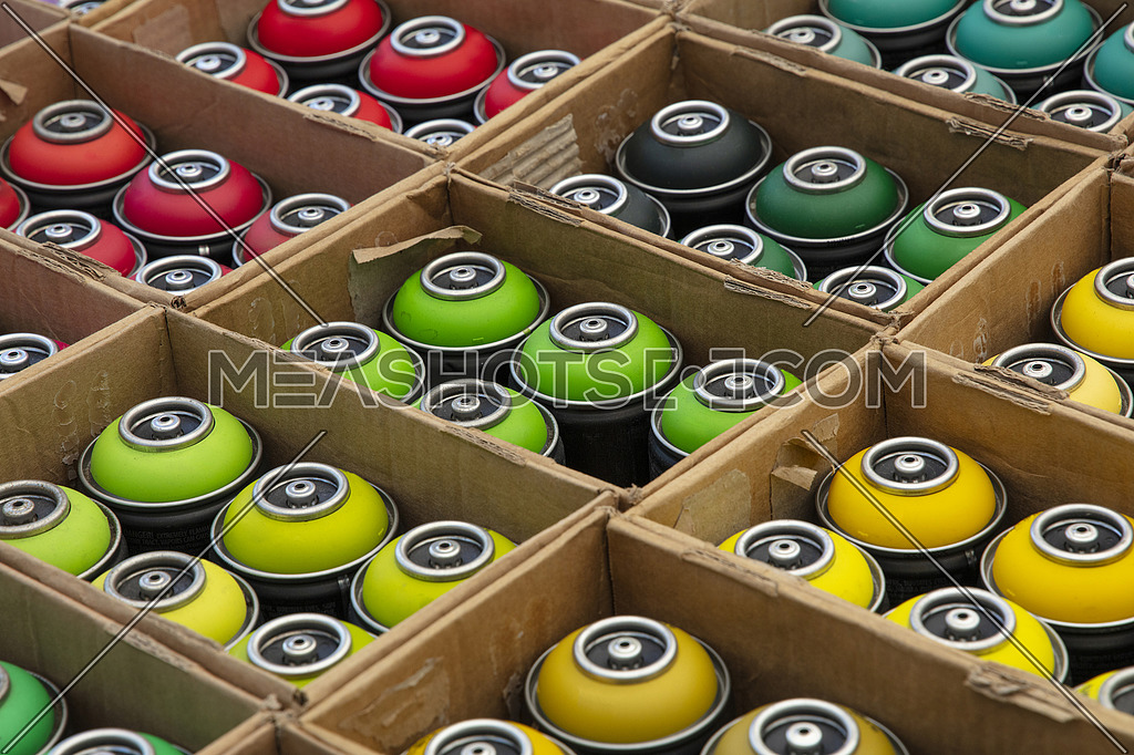 Selection of assorted colors graffiti spray paint cans in cardboard boxes at retail display of open market, high angle view