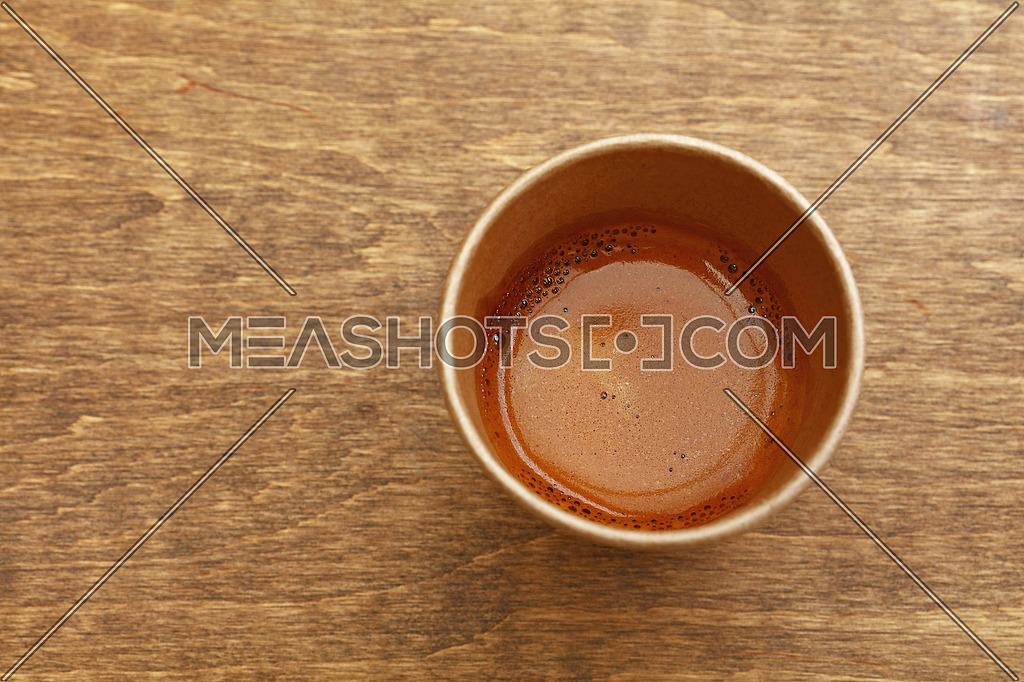 Close up one disposable brown paper cup full of espresso coffee on wooden table, elevated top view, directly above