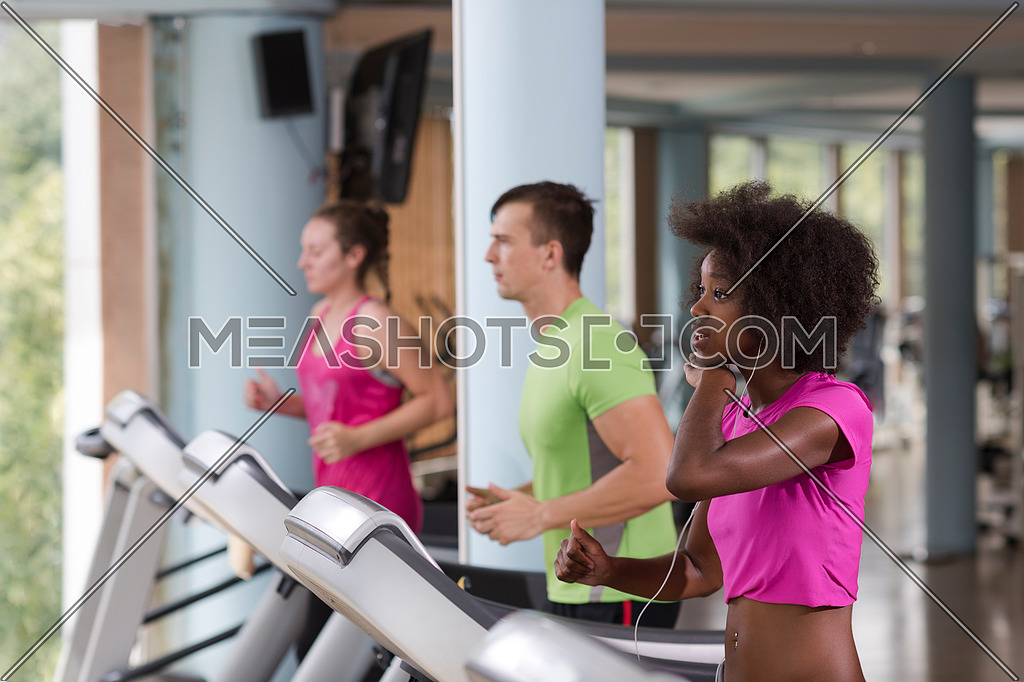 young people exercisinng a cardio on treadmill running chine in modern gym