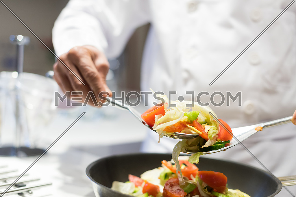 hands chef while preparing a meal of vegetables with satisfaction