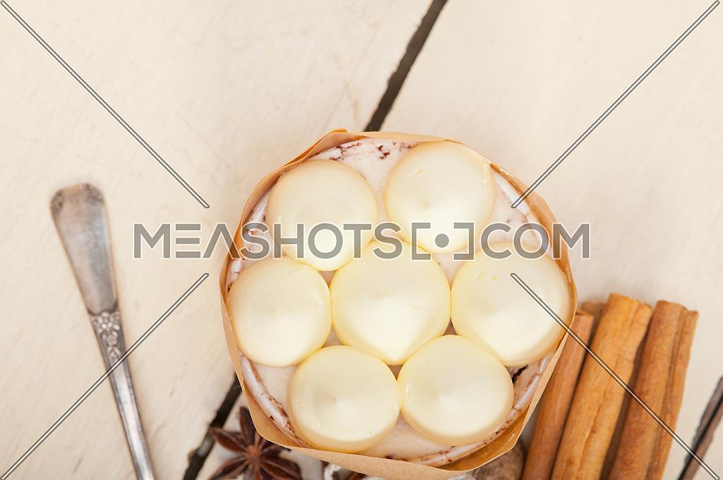 fresh vanilla and spice cream cake dessert over a rustic white wood table