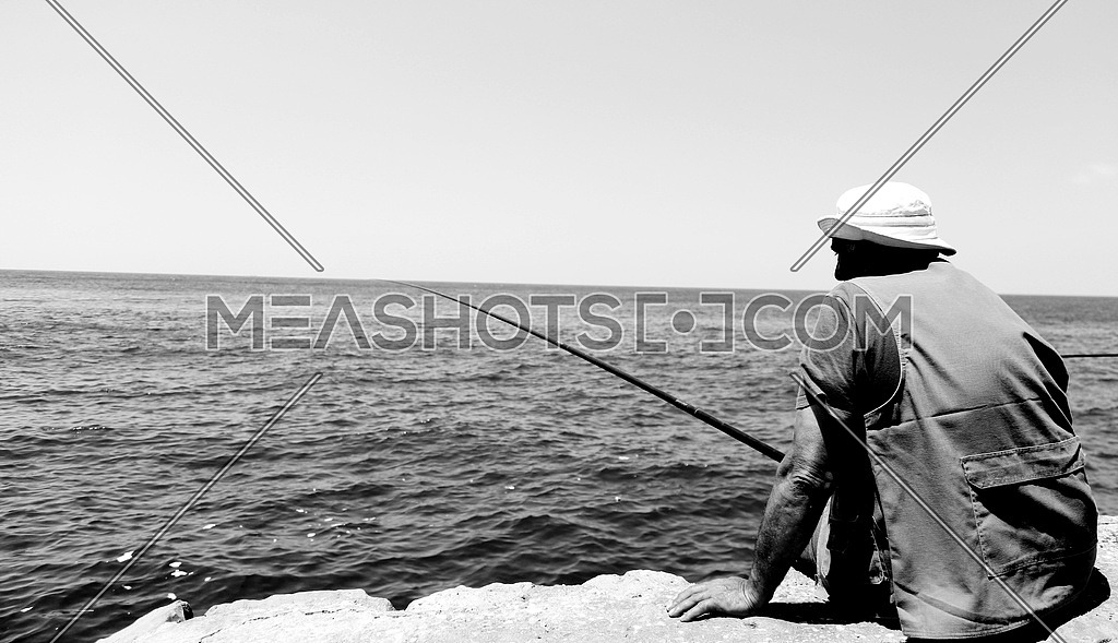 Man siting on the shore fishing in the sea