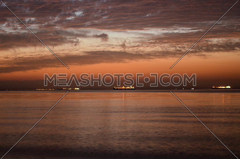 a beautiful lone exposure frame of the sea showing ships and their lights reflecting on the water and heavy clouds in the sky