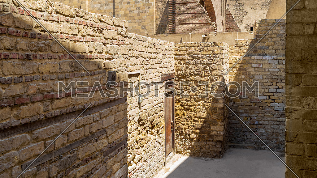 Old stone building with entrance door on narrow deadlock street of medieval town with sunlight