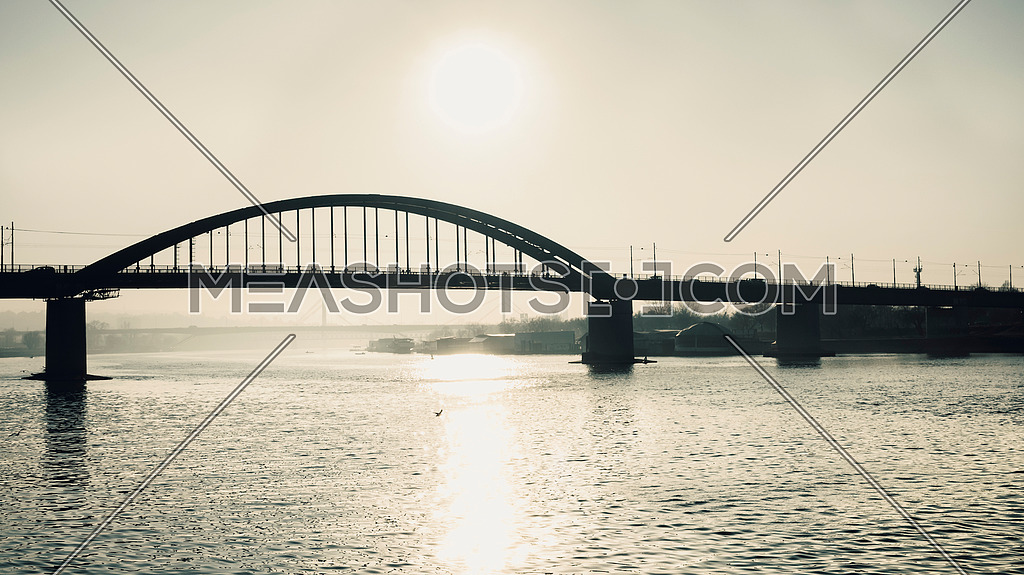 Sun reflection in the river with bridge in foggy background
