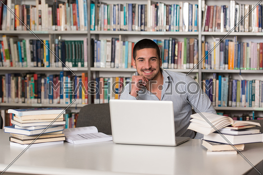 In The Library - Handsome Male Student With Laptop And Books Working In A High School - University Library - Shallow Depth Of Field