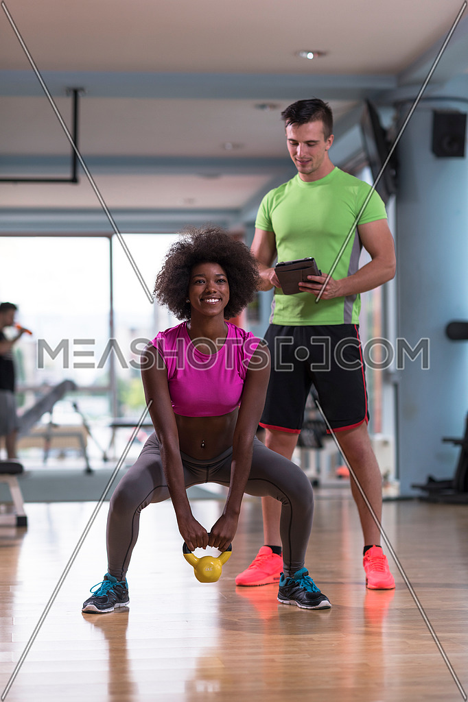 healthy young couple in crossfit gym weights workout with personal trainer