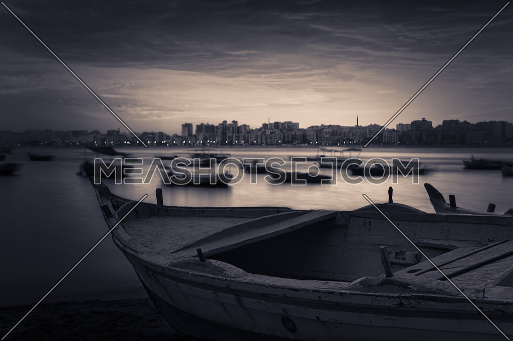 Fishing boat on the beach at sunrise with Alexandria skyline in far distance and cloudy sky at sunrise