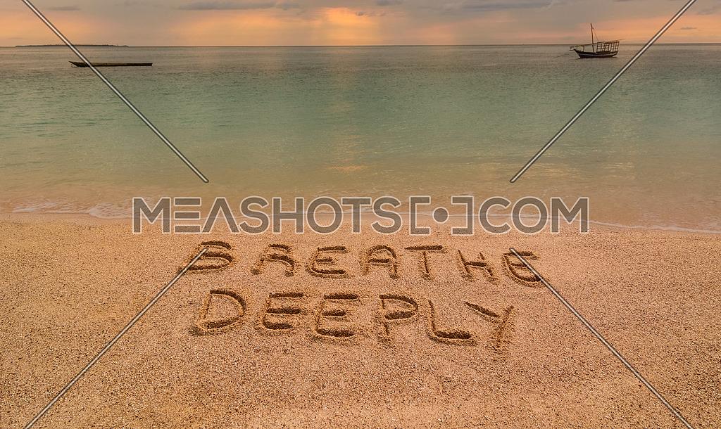 In the photo a beach in Zanzibar at sunset where there is an inscription on the sand \