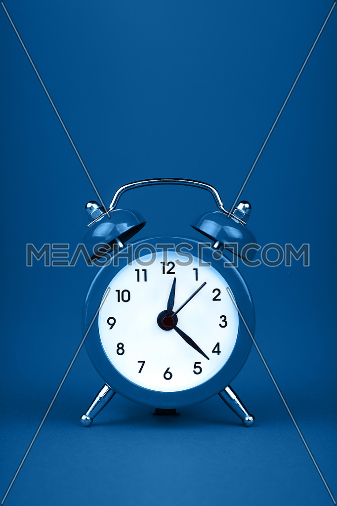 Close up one small blue metal twin bell retro classic alarm clock over blue paper background with copy space, low angle front view