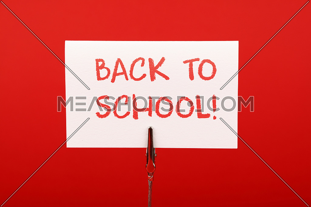 Back to school white crayon handwritten sign over red paper background with copy space