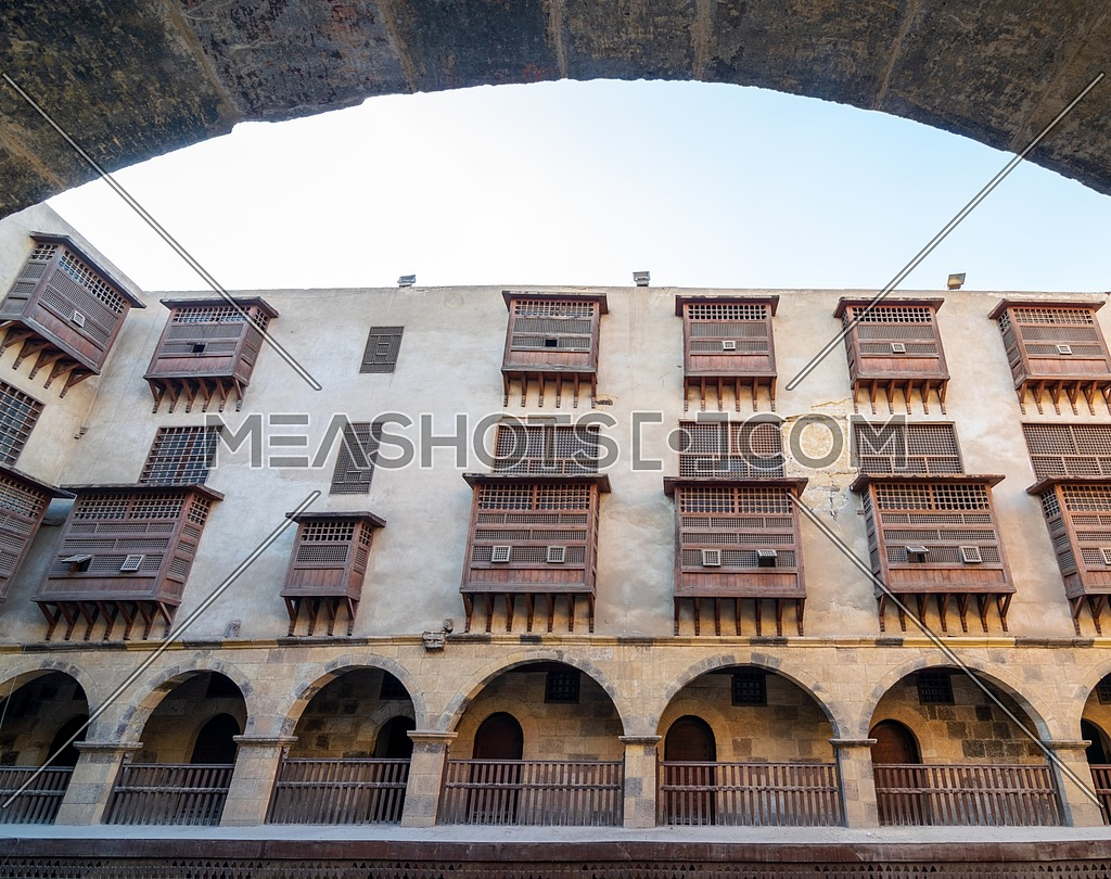 Facade of historic Wikala of Bazaraa building through stone arch , with vaulted arcades and oriental wooden oriel windows, suited in Tombakshia street, Gamalia district, Medieval Cairo, Egypt