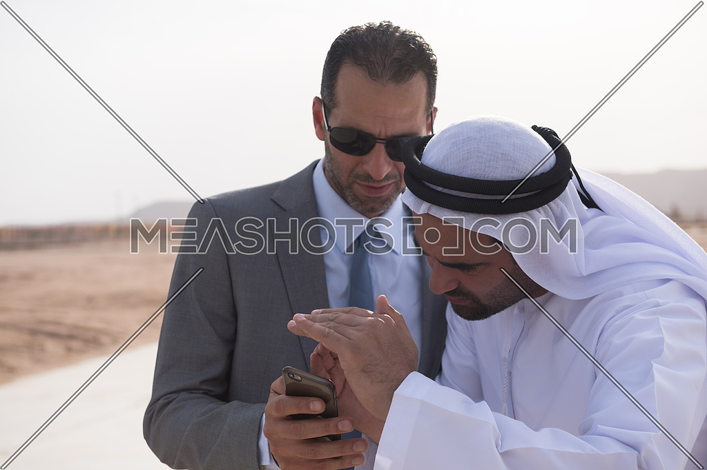 young successful middle eastern businessman looking with Arab business partner in the phone