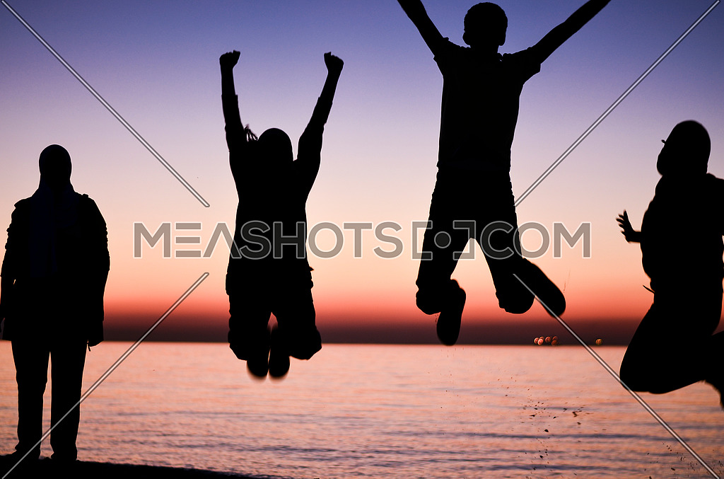 four friends enjoying their time, having fun and jumping at the beach during sunset
