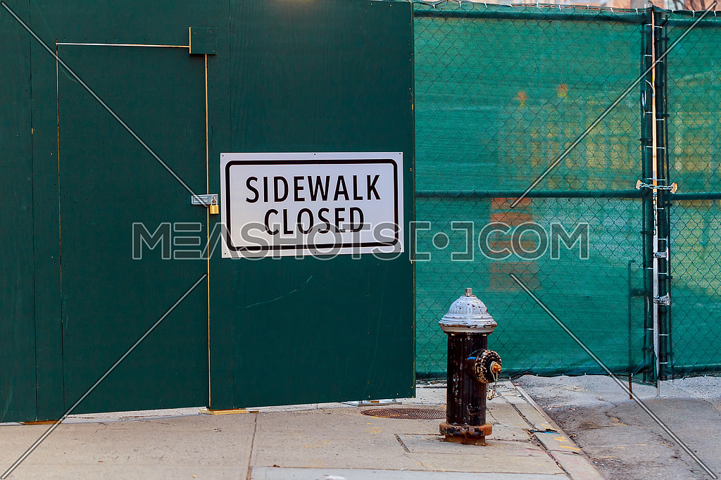 SIDEWALK CLOSED sign posted on green construction wall barrier. Horizontal.