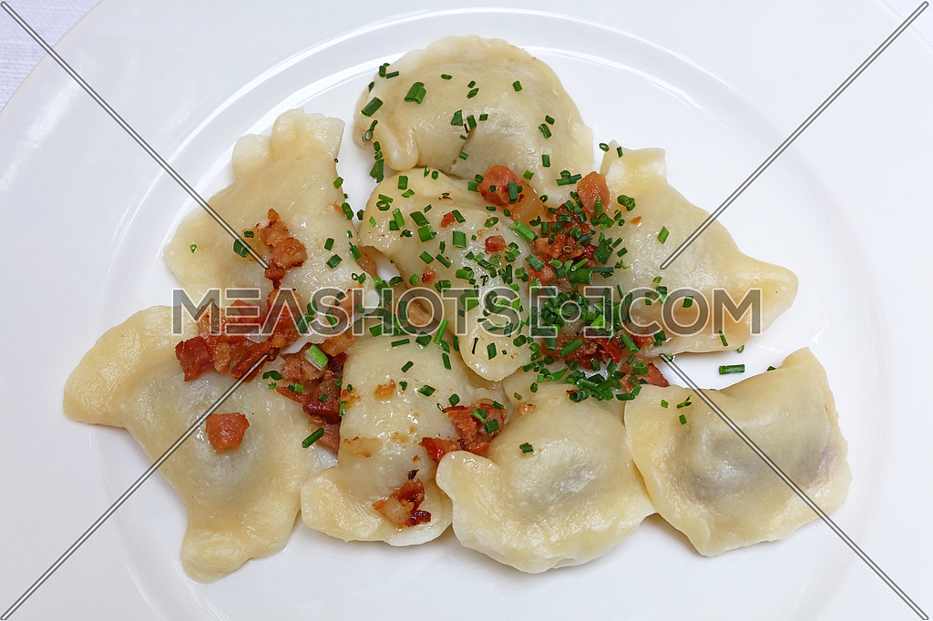 Plate of pierogi or varenyky stuffed filled dumplings with bacon crisps and green chive onion, traditional East Europe cuisine meal popular in Poland, Ukraine, Slovakia and Russia, close up, elevated top view