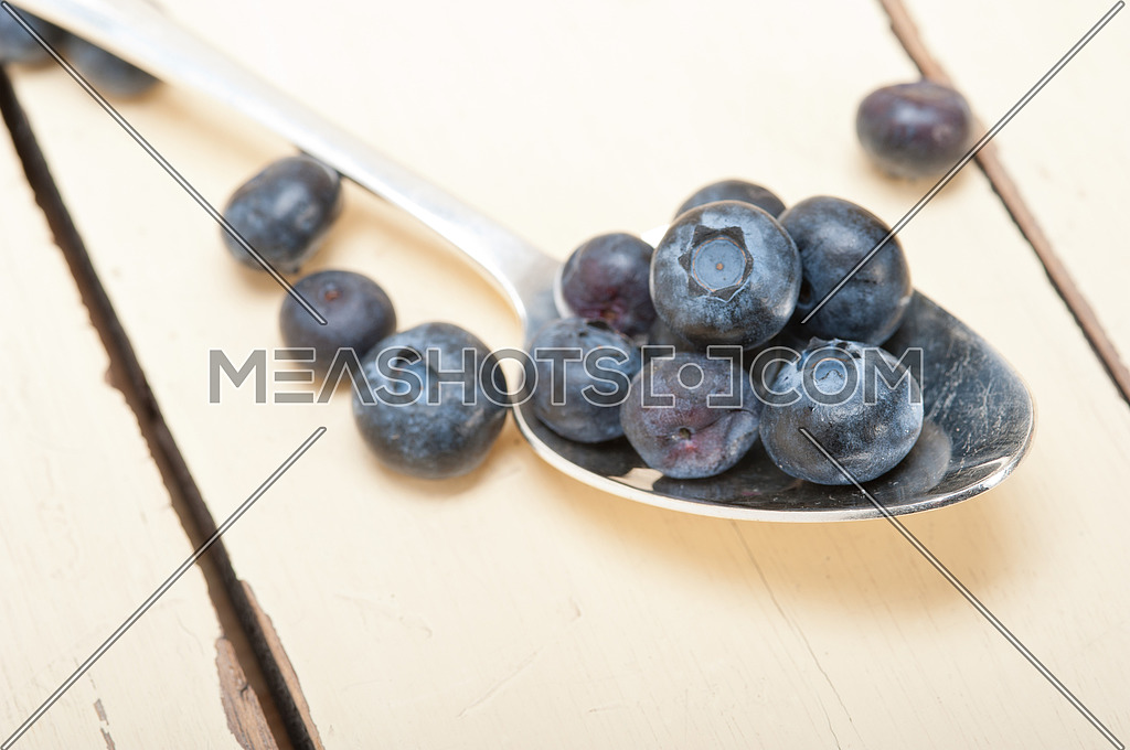 fresh blueberry on silver spoon over a white rustic wood table
