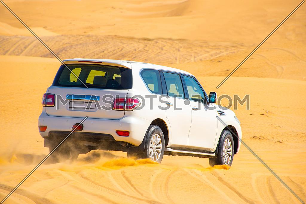 An SUV dune bashing in the desert
