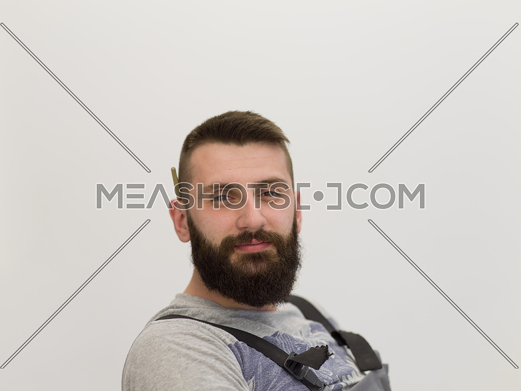 portrait of bearded hipster handyman with pen behind ear isolated on white background