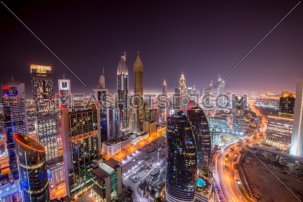 Dubai At night DIFC area in downtown showing sheikh zayed road and emirates towers