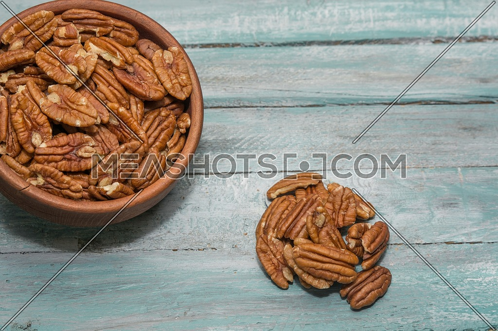 Tasty pecan in wooden bowl on the old background