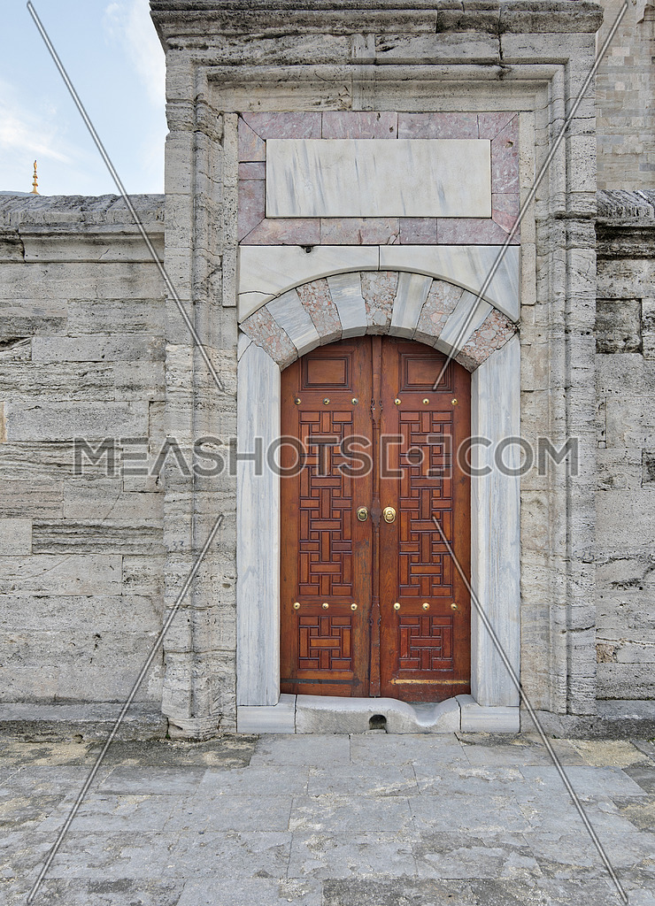 Wooden aged vaulted engraved door and exterior stone wall, Suleymaniye Mosque, Istanbul, Turkey