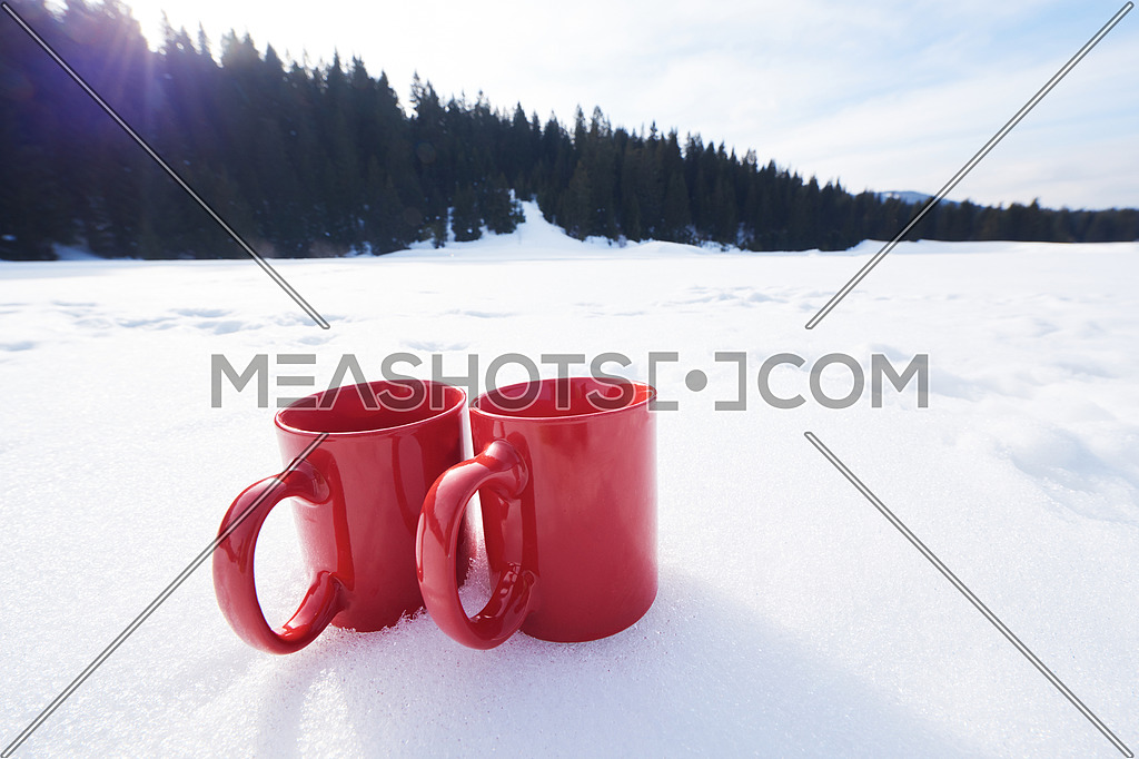 two red coups of hot tea drink in snow at beautiful winter sunny day scene with wooden house in background in forest