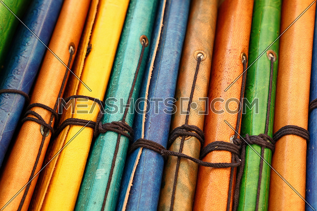 Close up many handmade colorful leather cover notebooks on retail display, high angle view