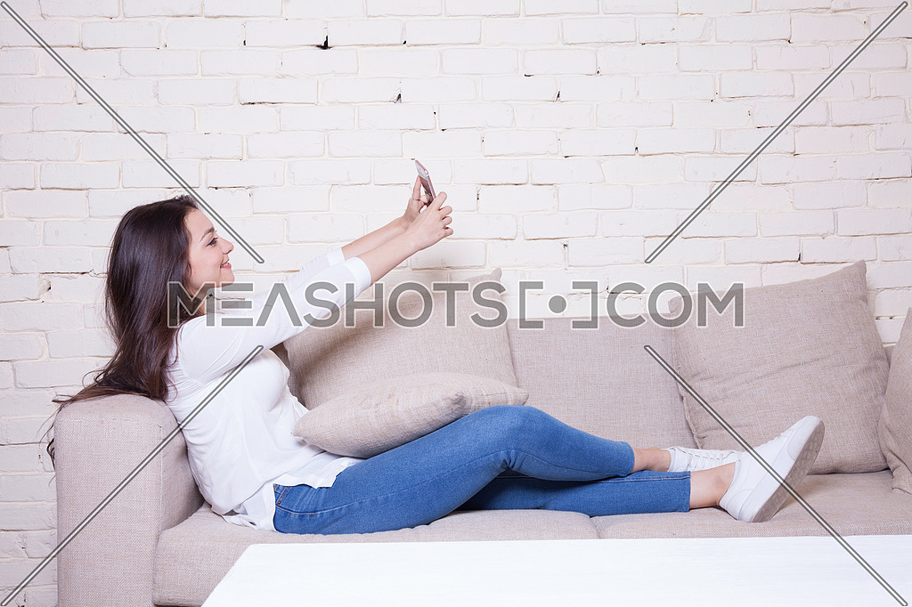 A girl sitting on a couch holding her mobile