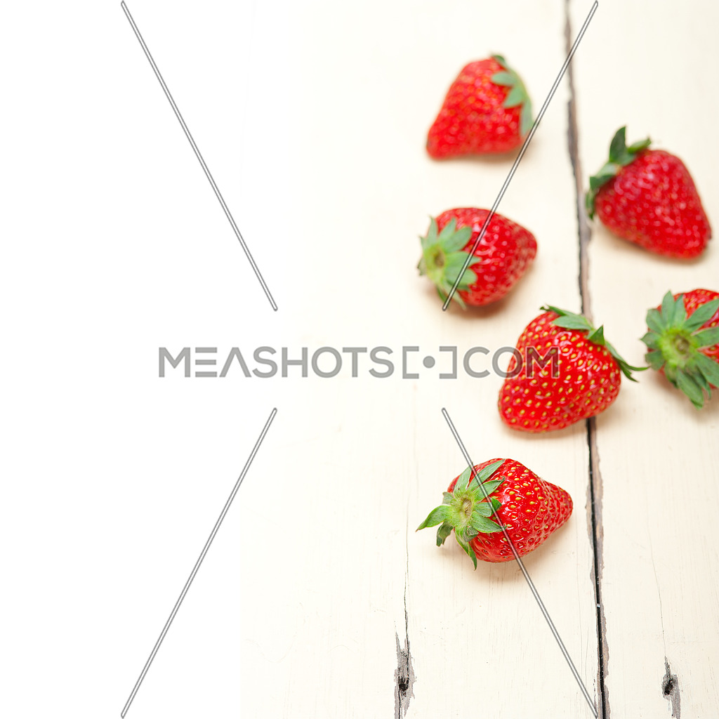 fresh organic strawberry over white rustic wood table