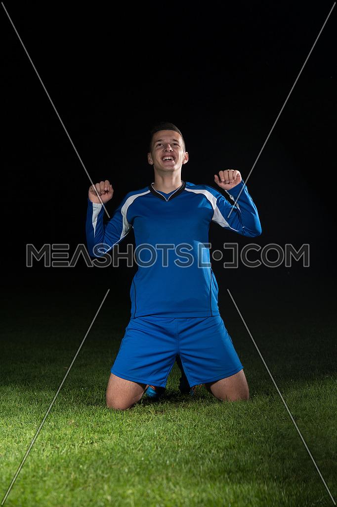 Man Soccer Player Celebrating Victory In Blue Uniform On Black Background