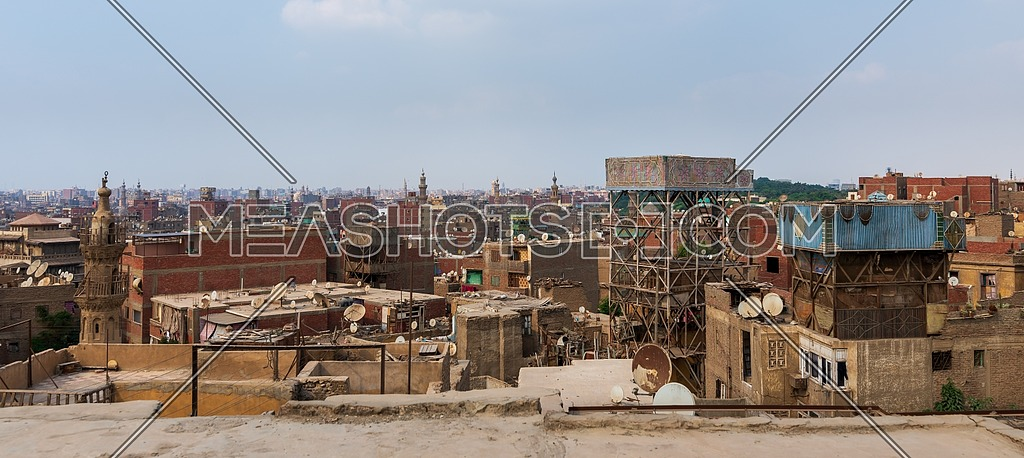 Shabby buildings with satellite dishes on rooftops located against blue sky in ancient city of Cairo, Egypt