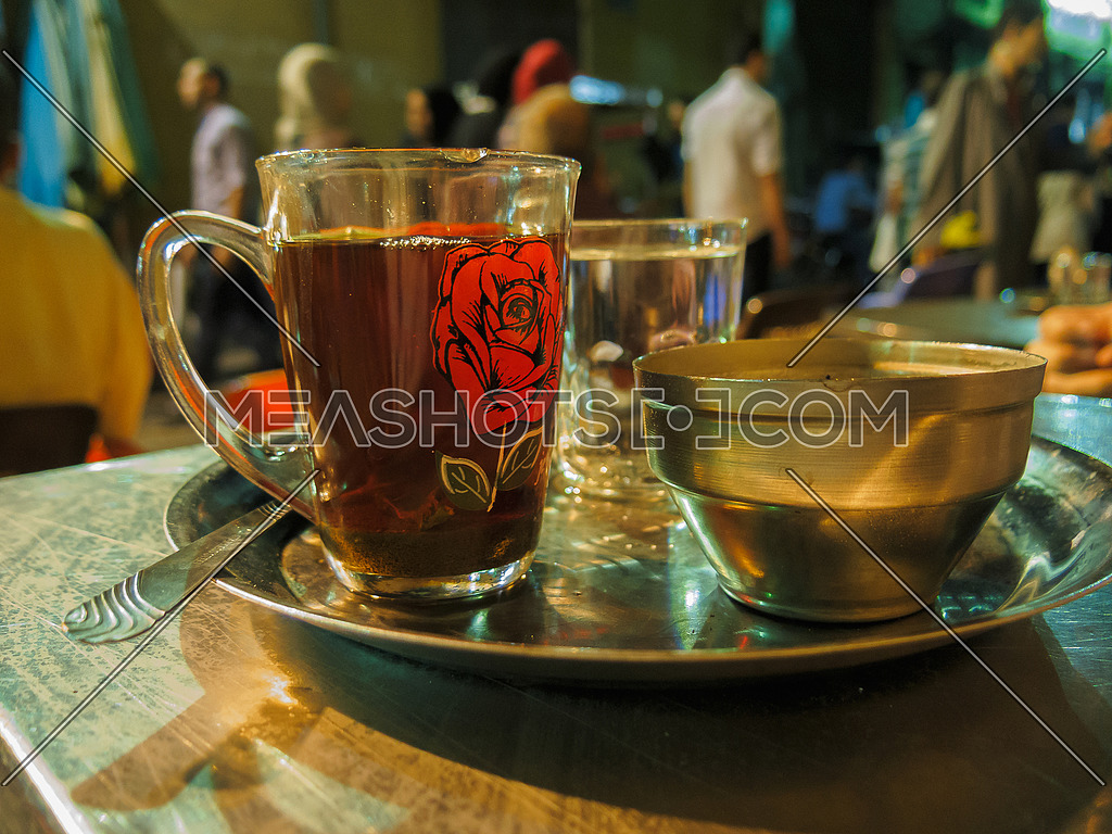 A traditional cup of tea and copper sugar bowl on a metal tray in an oriental street coffee shop
