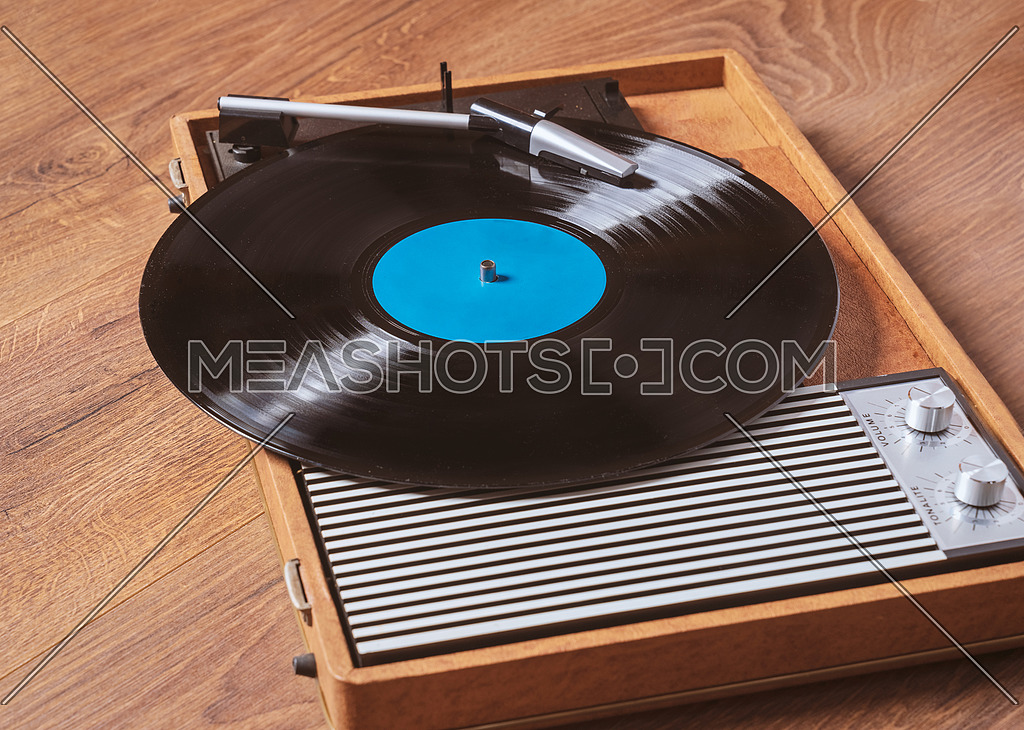 Older Gramophone with a vinyl record on wooden table,vintage style.