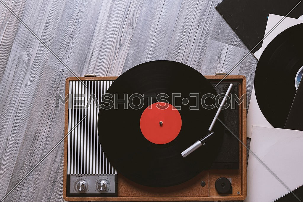 Vintage turntable with a vinyl record on gray wooden table, top view and copy space.