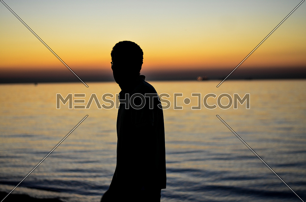 A guy standing at the beach enjoying his time and relaxing during sunset magic hour