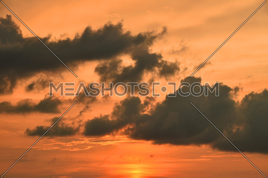 Beautiful dramatic orange sunset cloudscape with fluffy clouds over clear sky, low angle view