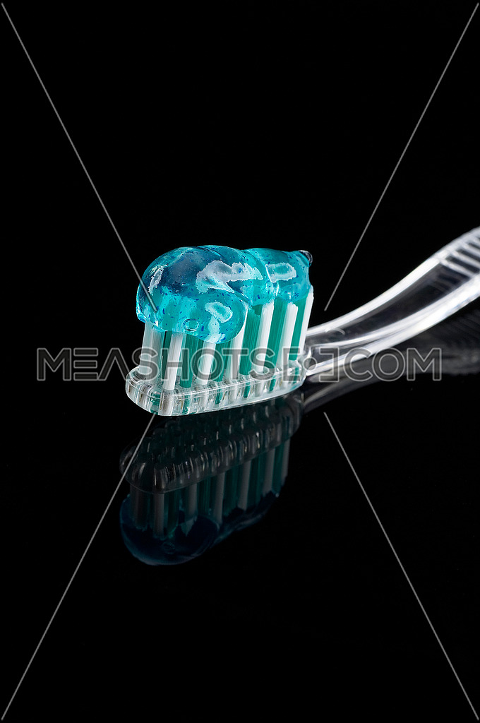 toothbrush and paste over black reflective background