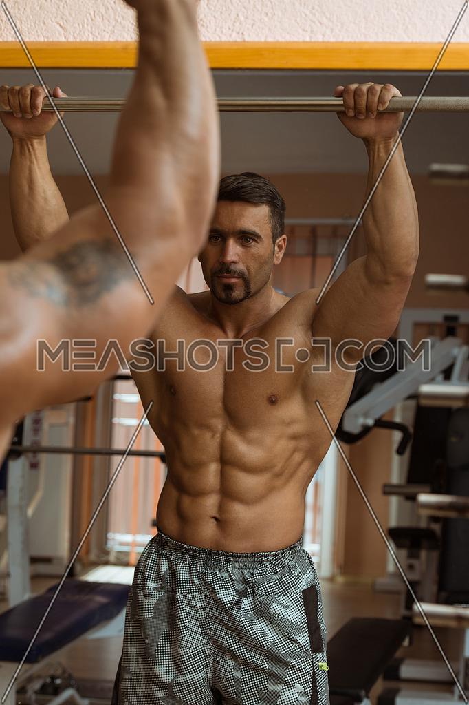 Muscular Man Flexing Abdominal Muscles Abs In A Health Club