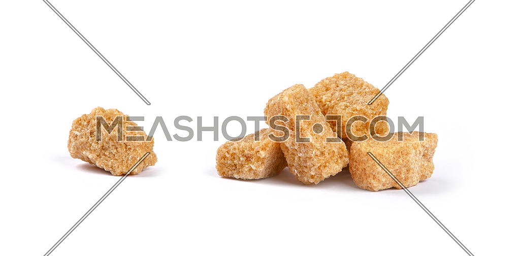 Close up group of brown demerara sugar cubes isolated on white background, side view